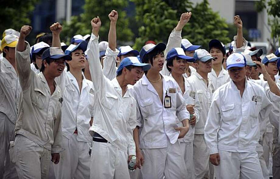 In this photo taken Monday June 7, 2010, workers at Foshan Fengfu Autoparts Co. a supply factory to Honda Motor's joint-ventures in China, raise their hands as they strike to demand for higher wages in Foshan in south China's Guangdong province.  Honda Motor Co. said Tuesday, June 8, 2010 it was assessing the impact of the walkout by the workers at one of its parts suppliers in China, just days after resolving a strike that froze car production at four factories. Photo: AP