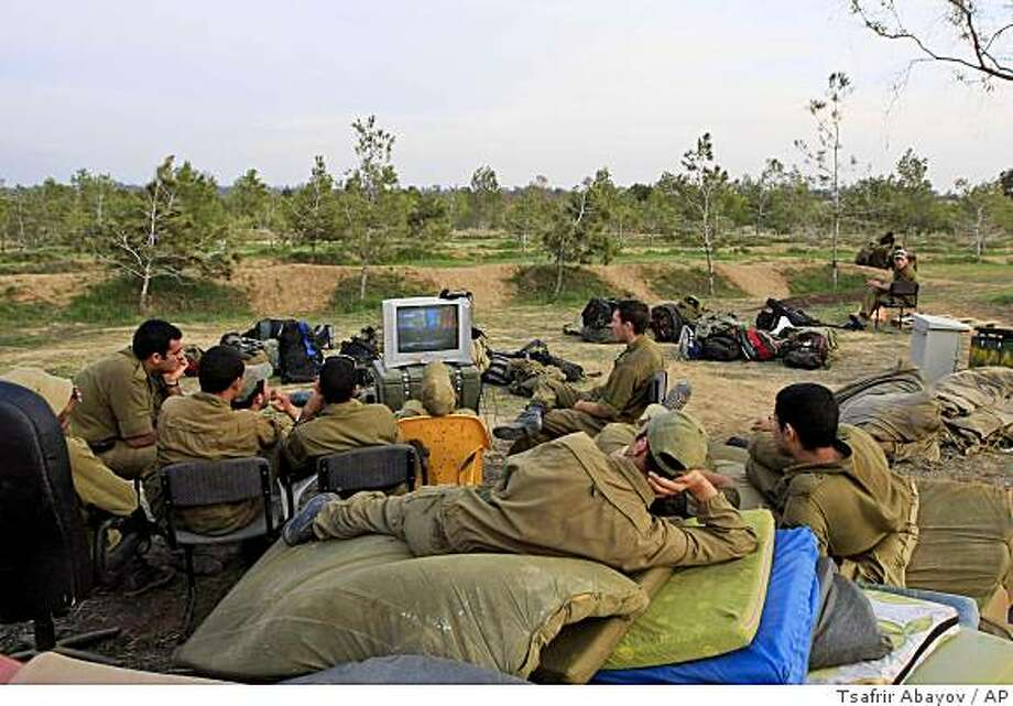 Israeli soldiers watch television near the Israel-Gaza border, Tuesday, Nov. 18, 2008. Israeli tanks forged into the southern Gaza Strip on Tuesday, drawing mortar fire from Palestinian militants and intensifying violence that has chipped away at a tenuous cease-fire.  Israel and Hamas have been trading fire for two weeks after nearly five months of relative quiet. The June 19 truce is due to expire next month, and both sides might be trying to dictate more favorable terms in anticipation of the agreement's renewal.(AP Photo/Tsafrir Abayov) Photo: Tsafrir Abayov, AP