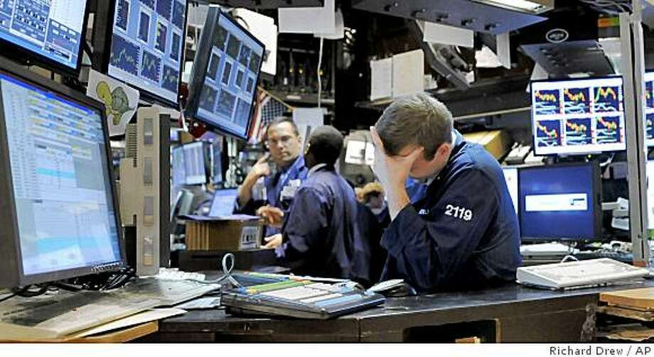 Specialist Charles Jenness, right, works at his post on the floor of the New York Stock Exchange Monday, Nov. 17, 2008. Wall Street finished sharply lower Monday as investors pored over more signs of economic weakness, including a huge round of layoffs in the financial sector. (AP Photo/Richard Drew) Photo: Richard Drew, AP