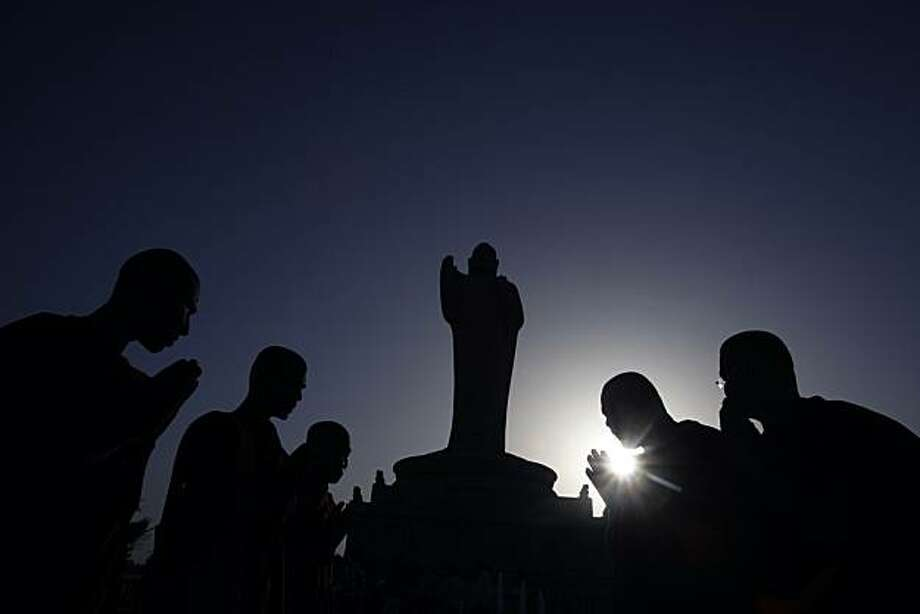 Buddist monks offering prayers to a Buddha statue are silhouetted against the setting sun on the occasion of Buddha Poornima in Hyderabad, India, Thursday, May 27, 2010. Buddha Poornima commemorates the birth, enlightenment and demise of Buddha. Photo: Mahesh Kumar A, AP