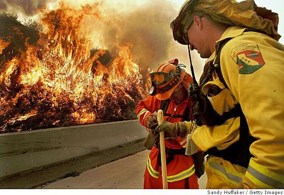 DIAMOND BAR, CA-NOV.16:  Firefighters battle a blaze November 16, 2008 in Diamond Bar, California.  Several fires have grown together in this area to create what is now called the Triangle Complex Fire. Over 40,000 people have been evacuated in the path of the fire which has damaged or destroyed more than 160 homes so far. Strong Santa Ana Winds are fueling major wildfires in five southern California counties that have destroyed hundreds of homes and charred thousands prompting California Governor Arnold Schwarzenegger to declare multiple states of emergency.  (Photo by Sandy Huffaker/Getty Images) Photo: Sandy Huffaker, Getty Images