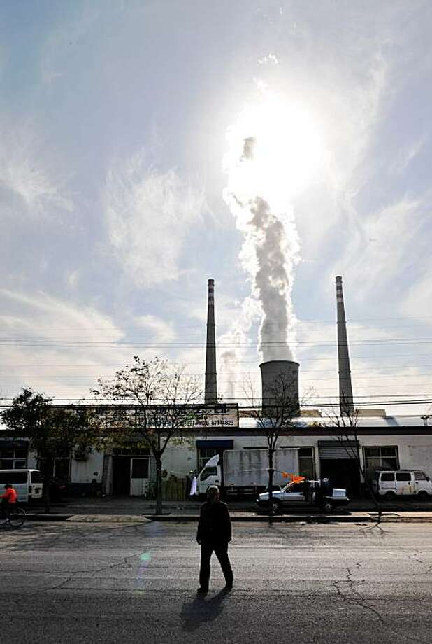 Coal powers  three-quarters of China's industry  and without it most ordinary  Chinese would be sitting in the  dark.   A woman crosses a street near a coal-fired power station on the outskirts of Beijing on November 7, 2008. Chinese Premier Wen Jiabao and a top UN official urged industrialised nations to alter lifestyles and investment modes as part of efforts to tackle global warming while opening a two-day international meeting on global warming in the Chinese capital, attended by representatives from 76 nations who are focusing on technology transfer mechanisms that many hope will be enshrined in a new global treaty on reducing greenhouse gas emssions. Scientists said in September that China had leapfrogged the United States as the world's biggest producer of carbon dioxide (CO2), one of the principal gases that cause global warming.AFP PHOTO/Frederic J. BROWN (Photo credit should read FREDERIC J. BROWN/AFP/Getty Images) Photo: Frederic J. Brown, AFP/Getty Images