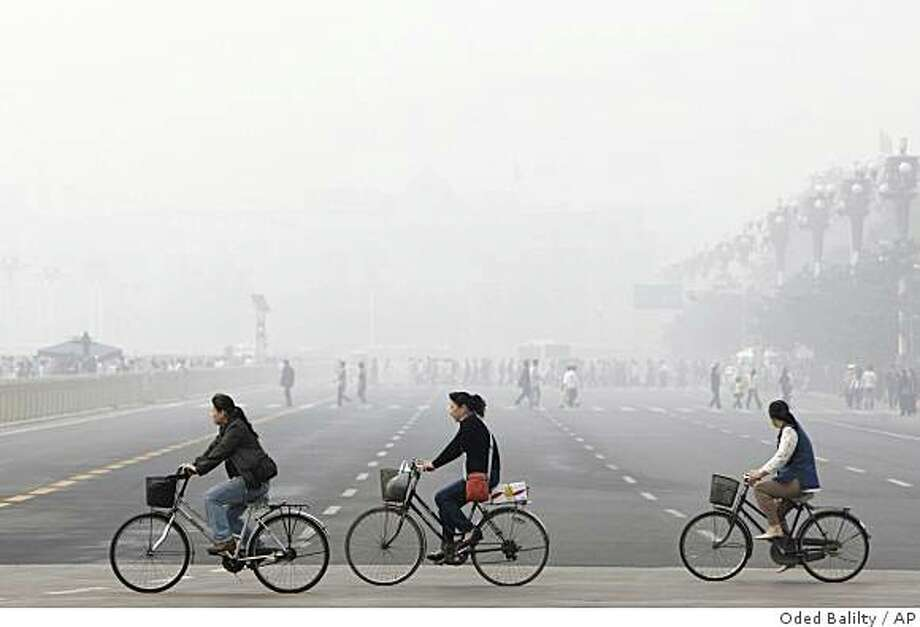 **FILE**This May 1, 2008 file photo shows Chinese women cycling through smog and pollution over Beijing's Tiananmen Square. A thick brown cloud of soot, particles and chemicals stretching from the Persian Gulf to Asia threatens health and food supplies in the world, according to a report commissioned by the U.N. Environment Program released Thursday, Nov. 13, 2008. (AP Photo/Oded Balilty, File) Photo: Oded Balilty, AP