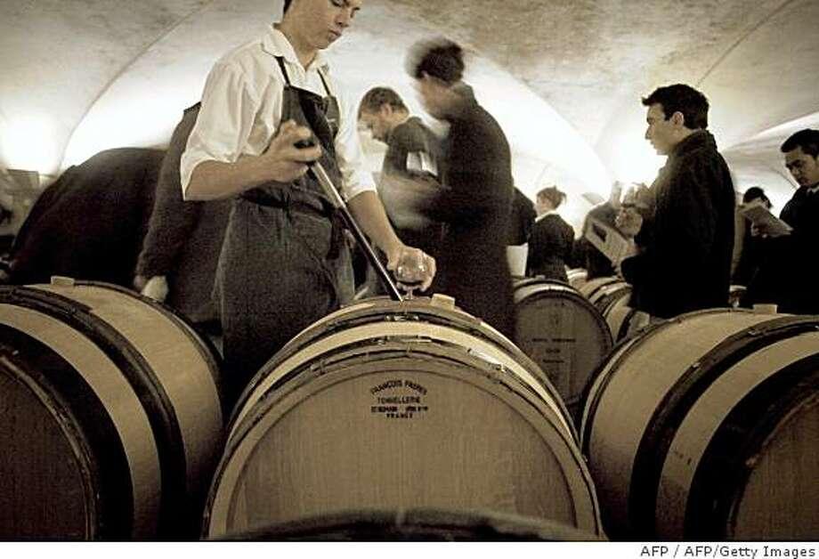 """Un caviste pr?l?ve du vin d'un f?t avant de servir un verre, le 18 novembre 2007 dans une cave des Hospices de Beaune, lors d'une d?gustation ouverte au public le jour de la traditionnelle vente aux ench?res du vin des hospice. Il s'agit de la 147e vente des vins des Hospices, organis?e par la maison Christie's qui adjugera la """"pi?ce du pr?sident"""",  (228 litres), un Beaune Premier Cru Cuv?e Nicolas Rolin, au profit de trois associations, dont l'une se consacre aux maladies orphelines. AFP PHOTO / JEFF PACHOUD (Photo credit should read JEFF PACHOUD/AFP/Getty Images) Photo: AFP, AFP/Getty Images"""