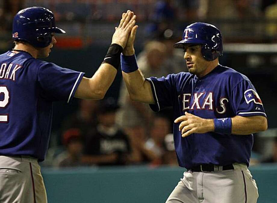 Texas Rangers' Justin Smoak, left, congratulates teammate Matt Treanor at the plate after they scored on a single hit by Michael Young in the eighth inning during an interleague baseball gam against the Florida Marlins in Miami, Wednesday, June 16, 2010.The Rangers won 6-3. Photo: Lynne Sladky, AP