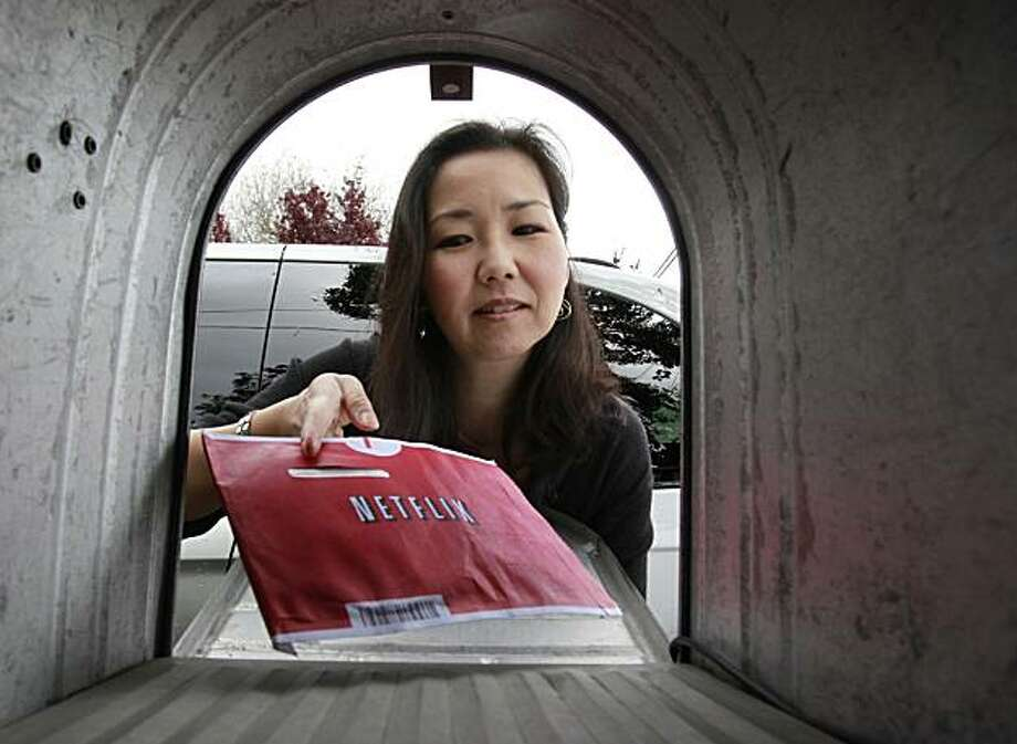 Netflix customer Carleen Ho poses with a Netflix movie she is picking up from her mail box in Palo Alto, Calif., Tuesday, April 20, 2010. Netflix Inc. releases quarterly earnings Wednesday, April 21, after the market close. Photo: Paul Sakuma, AP