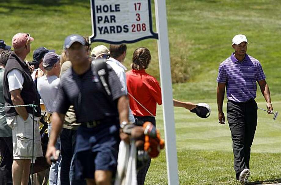 Tiger Woods walks to fourth tee as a spectator holds out hat for an autograph during a practice round at Pebble Beach Golf Course in Pebble Beach, Calif. on Sunday, June 13, 2010. Photo: Orville Myers, AP