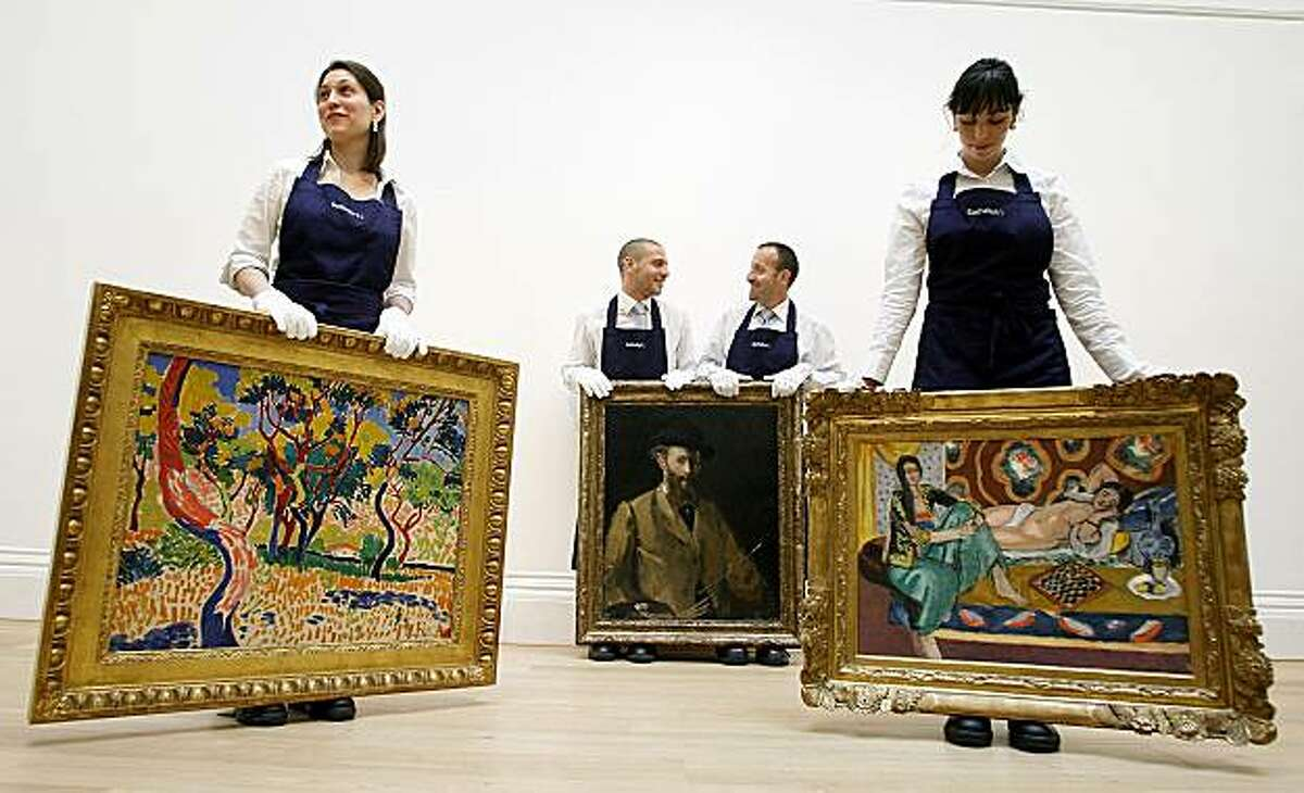 ** CORRECTS SPELLING OF ABRES A COLLIOURE ** Employees display paintings of Edouard Manet's Self Portrait with a Palette, centre, estimated at 20-30 million pounds, $29-43.4 million, Henri Matisse's Odalisques Jouant Aux Dames, which is estimated at 10-15million pounds, $14.5-21.7 million right, and Andre Derain's Arbres a Collioure, estimated to fetch 9-14 million pounds, $13-20.3 million, during a photocall at Sotheby's, in London, Friday, June, 11, 2010. These paintings will go under the hammer during the Impressionist and Modern Art sales on June 22 .