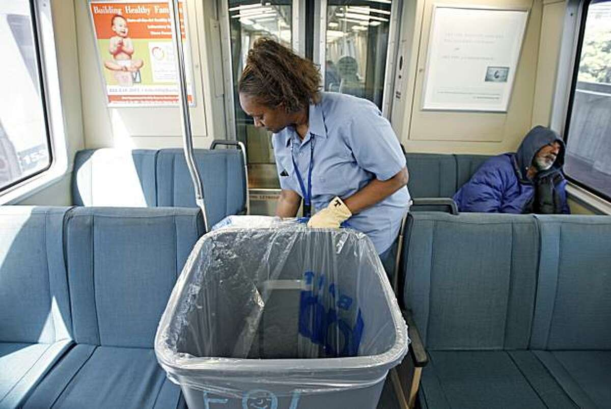 Theresa Williams, 55, rushes to clean a BART car at the Daly City BART station.