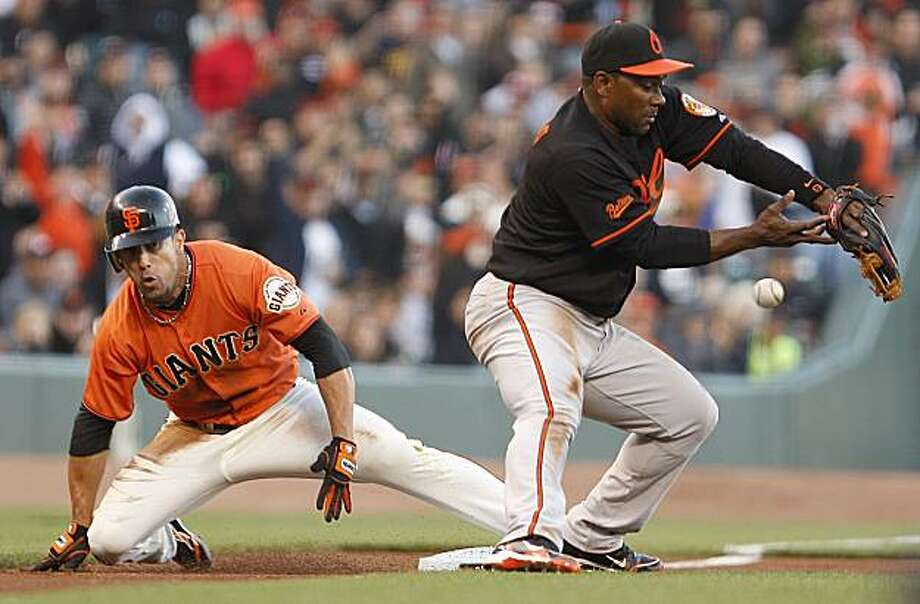 San Francisco Giants' Andres Torres, left, slides safely past Baltimore Orioles third baseman Miguel Tejada with a triple during the first inning of a baseball game Monday, June 14, 2010, in San Francisco. Photo: Ben Margot, AP