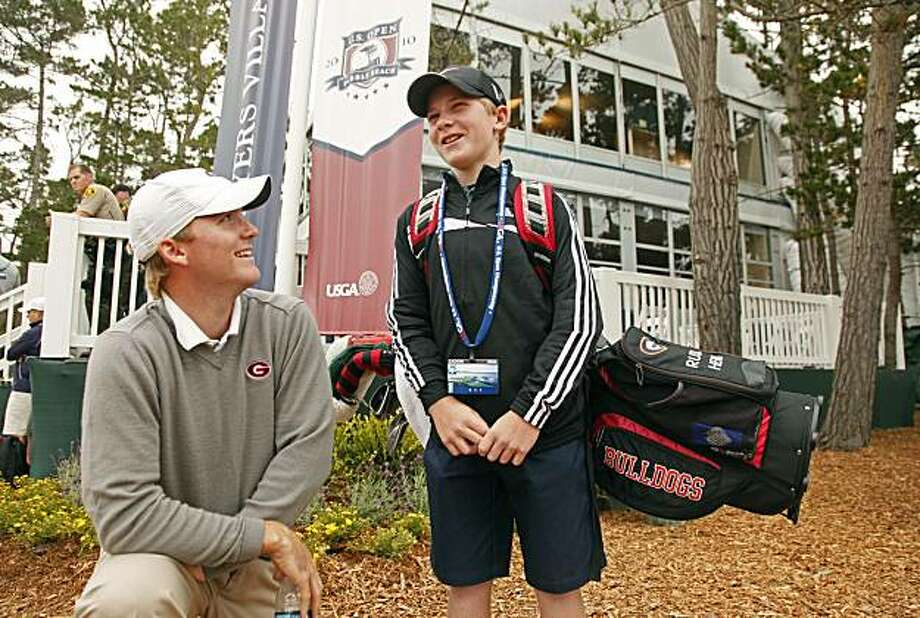 Russell Henley, left, of Macon, Ga., poses with his 13-year-old caddie, Jeffrey Aronson, right, of Los Angeles, before playing a practice round of the U.S. Open golf tournament in Pebble Beach, Calif., Monday, June 14, 2010. Henley, playing as an amateur,asked Aronson to be his caddie Monday after his brother was unable to make it to the tournament in time.  Aronson first met Henley while watching him play on Sunday. Photo: Eric Risberg, AP