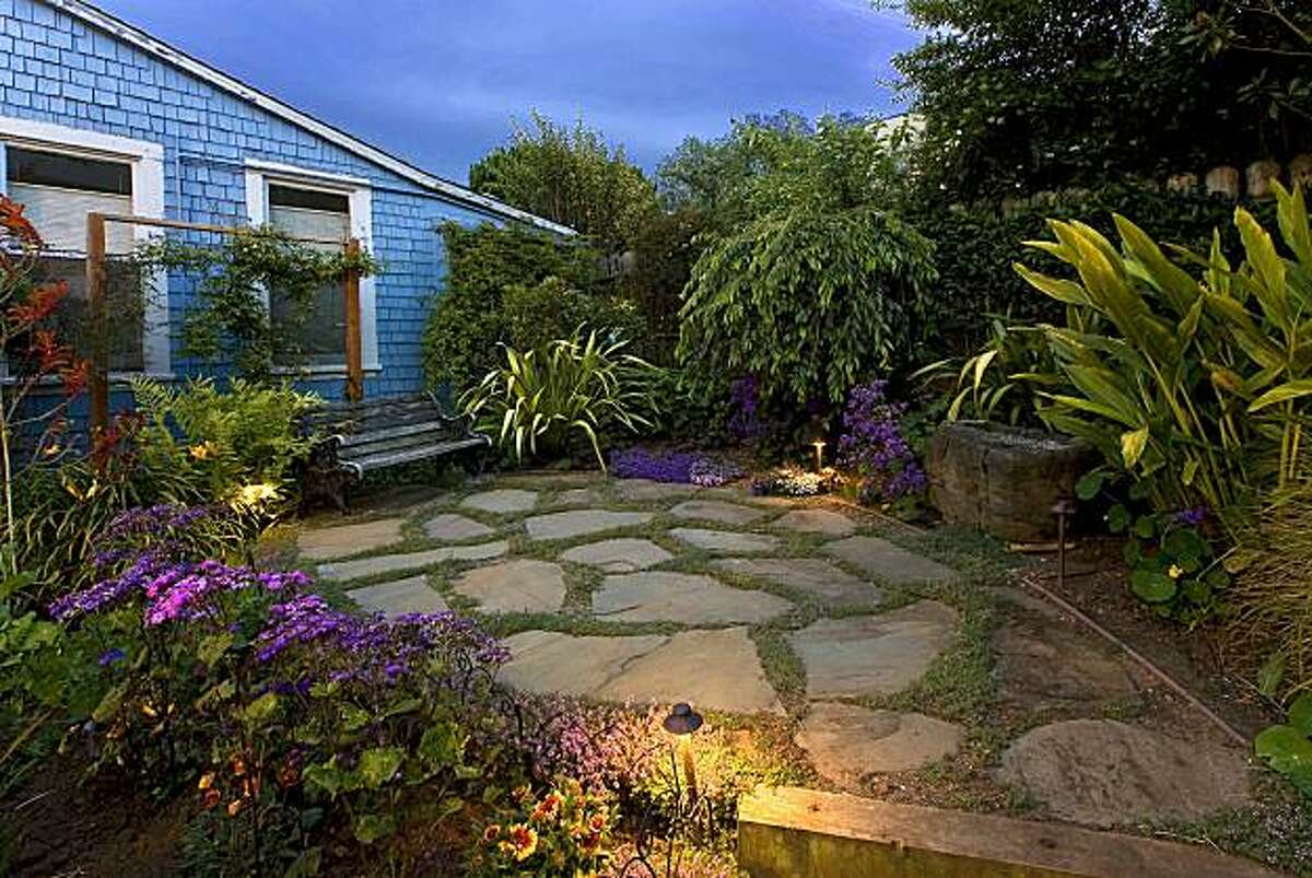 A rear garden features a stone patio. The Victorian home is listed for $1.699 million.
