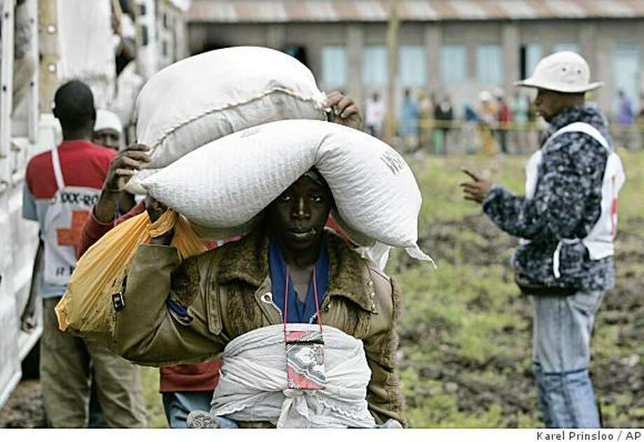 Displaced people carry sacks of flour during a Red Cross food distribution, Tuesday, Nov. 11, 2008, in Kibati,  just north of Goma in eastern Congo.  The humanitarian crisis in eastern Congo has exploded since rebel leader Laurent Nkunda launched an offensive Aug. 28, with around 50,000 refugees crowded around Kibati, packed into camps or sleeping out in the open, scrambling for the basics, including water to drink, wash, and cook.(AP Photo/Karel Prinsloo) Photo: Karel Prinsloo, AP
