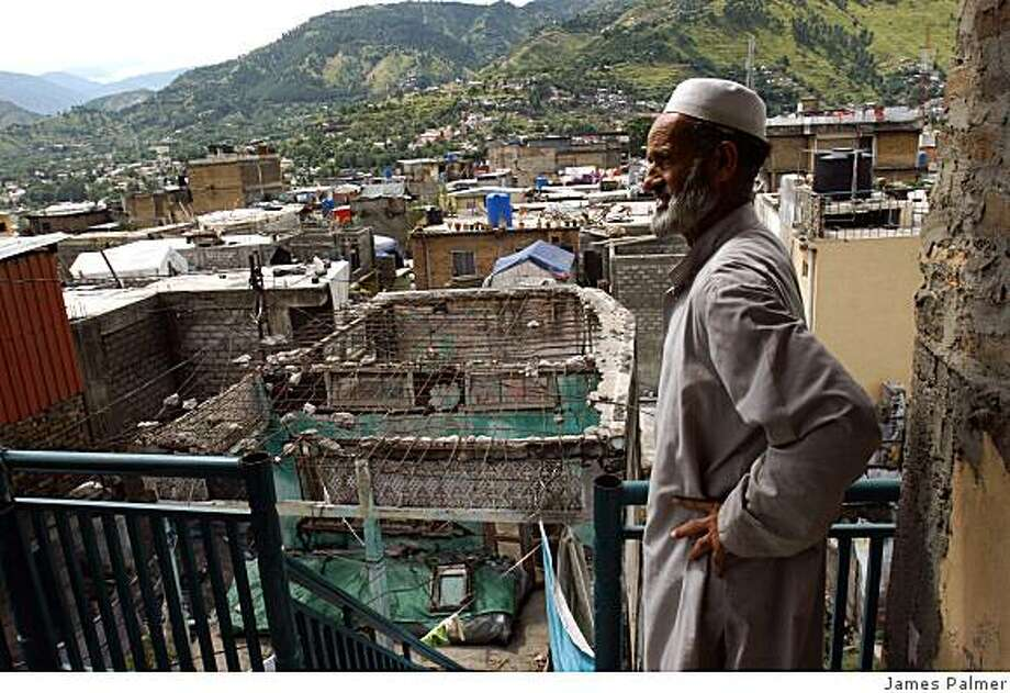 An elderly man standing on a balcony in Muzaffarabad, Pakistan, on  September 7, 2008, overlooking a house damaged in the 2005 earthquake. Residents and government officials complain reconstruction in the city is lagging since the 2005 earthquake.  According to Muzaffarabad�s development authority, only 450 of the estimated 1,500 houses have been rebuilt in the past three years � just 30 percent. Photo: James Palmer