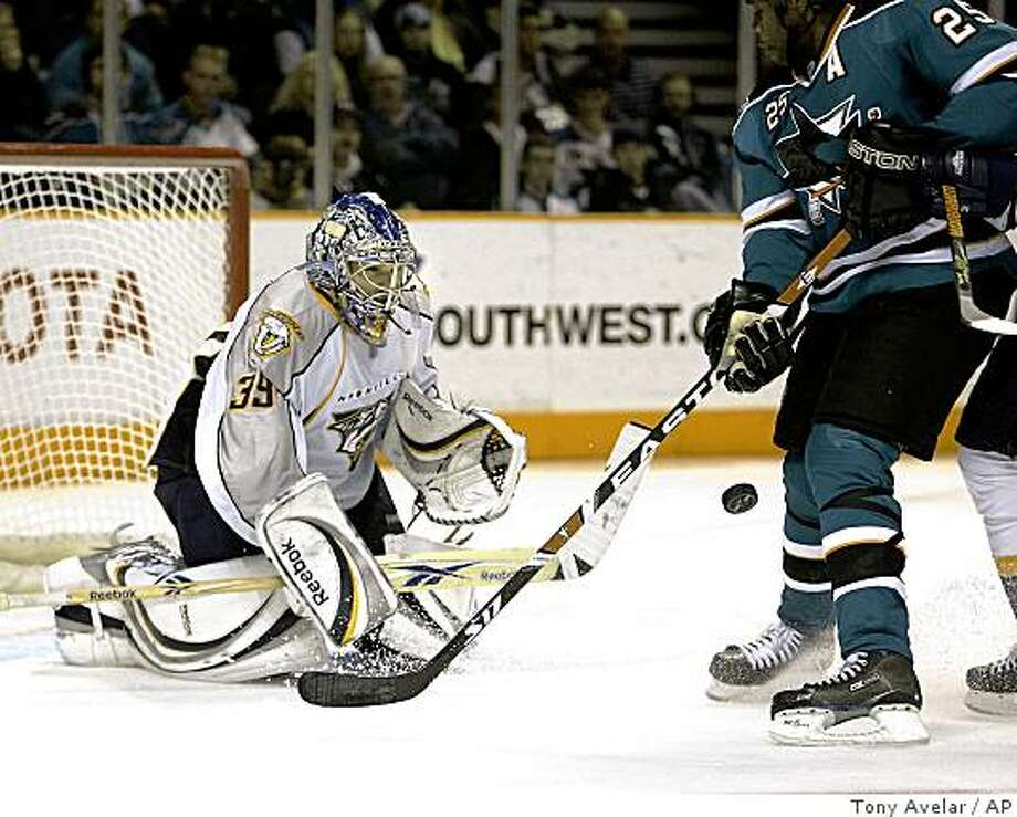 Nashville Predators goalie Dan Ellis, left, blocks a shot on goal by San Jose Sharks right wing Mike Grier, right, during the second period of an NHL hockey game in San Jose, Calif., Tuesday, Nov. 11, 2008. (AP Photo/Tony Avelar) Photo: Tony Avelar, AP