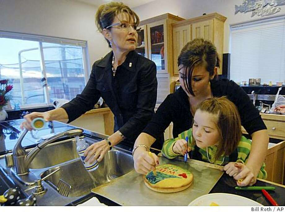 Alaska Gov. Sarah Palin mixes baby formula as her daughters Willow, 14, and Piper, 7, decorate a cake in the kitchen of their Wasilla,Alaska, home on Sunday, Nov. 9, 2008.  (AP Photo/Anchorage Daily News, Bill Roth) Photo: Bill Roth, AP