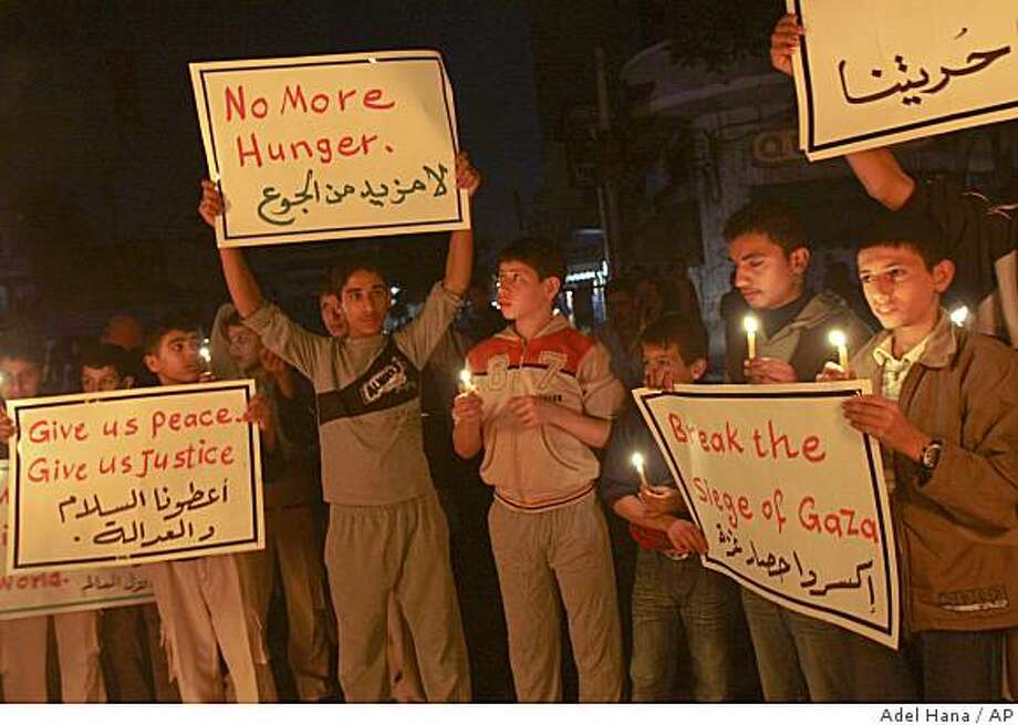 Palestinians hold candles and placards during a protest against Israeli sanctions,  at the main road in Gaza City, Thursday, Nov.13, 2008. Gaza officials shut down their only power plant, cutting off electricity to much of the city of 300,000, after Israel canceled plans to ship in some diesel fuel for the plant as well as 30 trucks full of humanitarian supplies. The Israeli move came after Gaza militants fired at least eight rockets and some mortar shells at Israel on Thursday, according to the Israeli military. Placards read the same in English and in Arabic. (AP Photo/Adel Hana) Photo: Adel Hana, AP