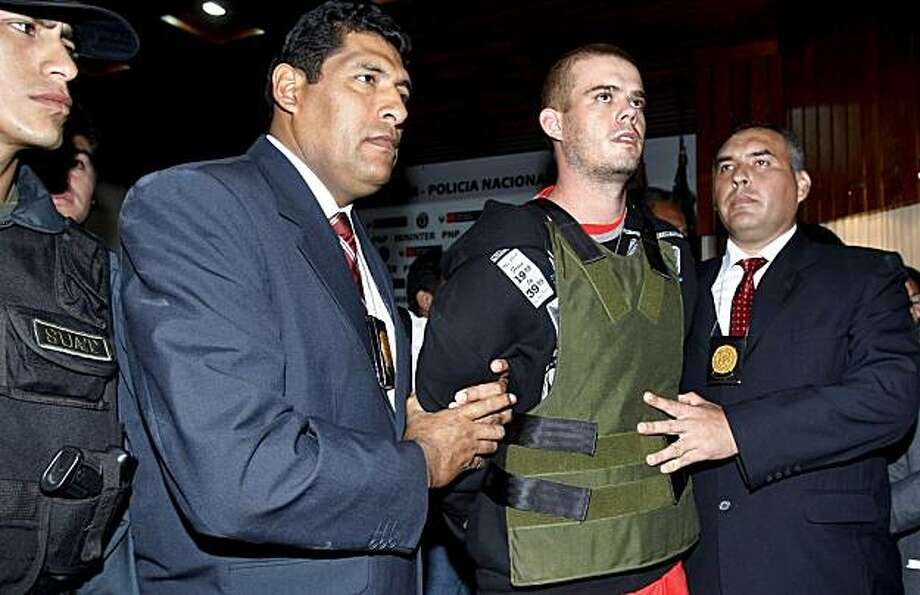 FILE in a June 5, 2010 file photo police officers escort Joran Van der Sloot, second right, during a press conference at a police station in Lima, Peru.   Peruvian police said Tuesday June 7, 2010 that Joran van der Sloot has confessed to killing a youngwoman in his Lima hotel room last week. Photo: Karel Navarro, AP