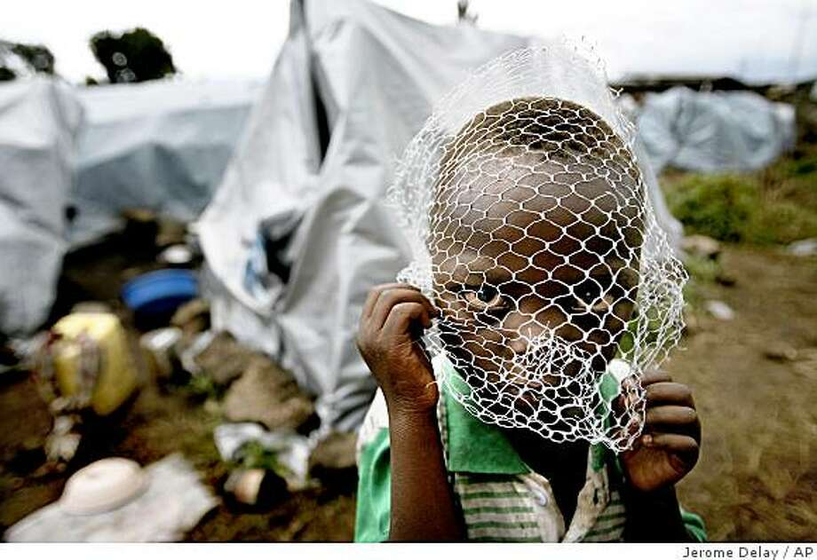 "Three year old Prospere  covers his face with a net ""against mosquitoes""  at the Kituku displaced camp in Goma, eastern Congo,  Monday, Nov. 10, 2008. Augustin came with over 200 families of park rangers from the Virunga national park one month ago, fleeing fighting   between rebels and  government forces that has left tens of thousands of refugees desperate for international aid. (AP Photo/Jerome Delay) Photo: Jerome Delay, AP"