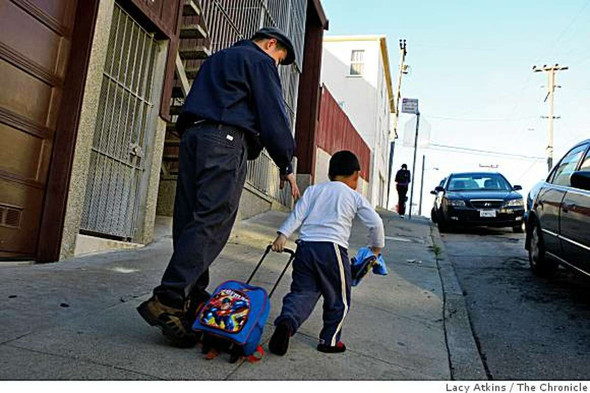Joe Tan watches over his son Thompson as they walk up to their car, Wednesday Nov. 12, 2008, from daycare in Visitacion Valley district in San Francisco, Calif.