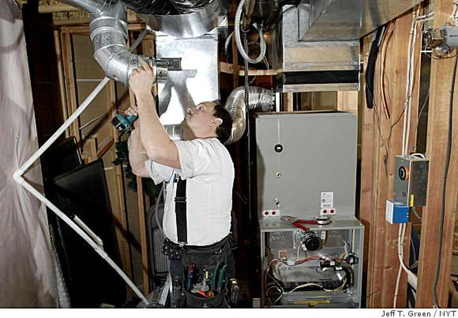 Don Honn installed fresh ductwork on Thursday, Oct. 13, 2005, for a new Trane gas furnace in Spokane, Wash., that replaced a 1991 version. With home energy bills expected to rise almost 50 percent this winter, the frugal American may face a tough call: the most effective way to cut that expense may be to spend thousands of dollars to replace an inefficient furnace. (Jeff T. Green/The New York Times) Photo: Jeff T. Green, NYT
