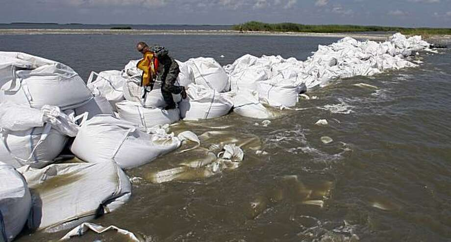 A guardsman walks along a barrier created by the National Guard from 2,000 pound bags of sand to block a pass in a effort to protect Scofield bay from oil from the Deepwater Horizon spill, Friday, June 11, 2010, near Venice, La.. Photo: Eric Gay, Associated Press