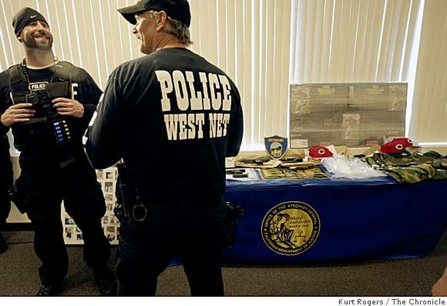 Unidentified police officers came in to look at the table of evidence that was laid out before a press conference that talked about gang arrests in multiple raids on Thursday, November 13, 2008 in Richmond, Calif. Photo: Kurt Rogers, The Chronicle