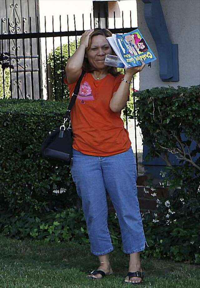 In this photo taken on Wednesday, Jun. 9, 2010, Prince Sagala covers her face as she arrives at her home in Montclair, Calif. Prince Sagala's first husband, Faustino Utrera, kidnapped their children 15 years ago: a daughter who was 3-years-old, at the time and their son 2-years-old. Sagala found them on Facebook. Utrera has been arrested in Florida, and their children are now in protective custody. Photo: Damian Dovarganes, AP