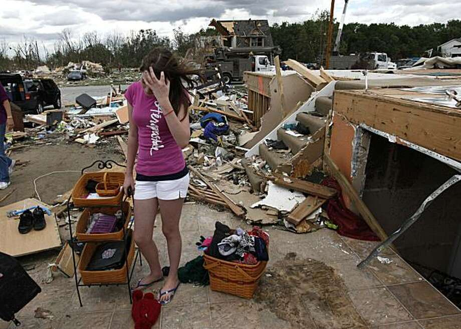 Billie Roelle, 14, stands at her home amid tornado debris in Millbury, Ohio Sunday, June 6, 2010. Authorities say tornados and thunderstorms that swept through the Midwest overnight killed a number of people in Ohio, destroyed 50 homes and damaged a highschool gymnasium where graduation was to be held Sunday. Photo: Paul Sancya, AP