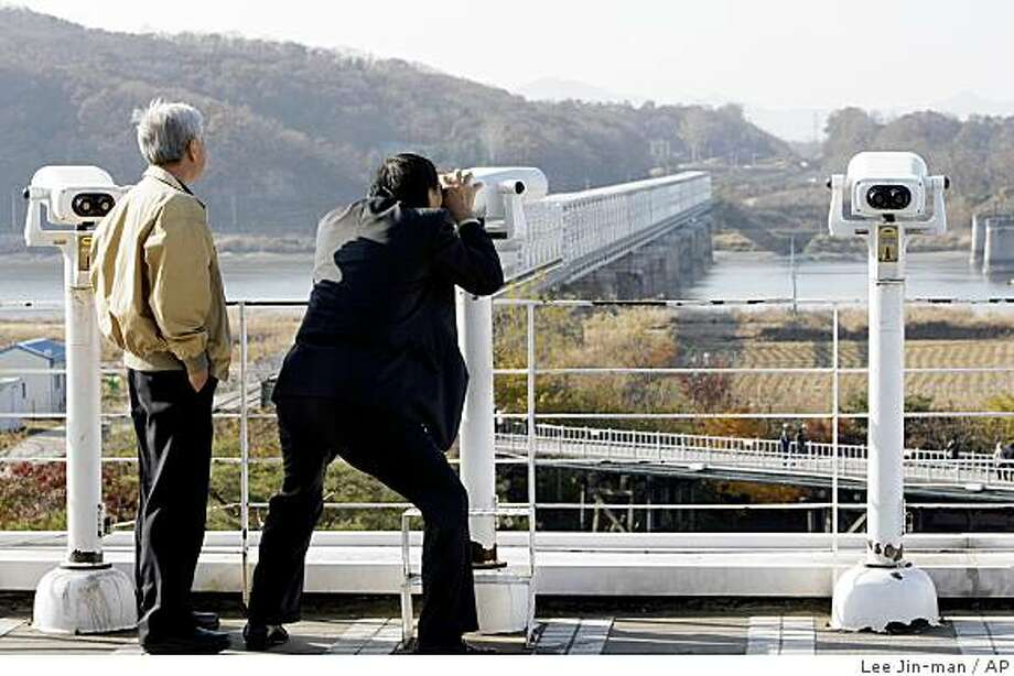 South Koreans use binoculars to look at the North side from Imjingak, an area near the border along the Demilitarized Zone that separates the two Koreas since the Korean War, north of Seoul, South Korea, Wednesday, Nov. 12, 2008. North Korea said Wednesday it will ban land crossings at its border with South Korea starting next month because of what it calls the South's confrontational stance _ a move that could doom a joint Korean industrial complex in the North.  (AP Photo/ Lee Jin-man) Photo: Lee Jin-man, AP