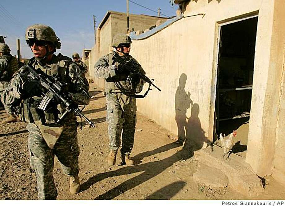 U.S. Army soldiers of Lightning Troop, 3rd Squadron, 3rd Armored Cavalry Regiment, walk, during a joint U.S-Iraqi army routine patrol, in Hay al Tinek neighborhood, northwestern Mosul, 360 kilometers (225 miles) northwest of Baghdad, Iraq, on Wednesday, Nov. 12, 2008. Two U.S. troops have been killed and six wounded Wednesday, in a shooting incident in Mosul, the U.S. army said. (AP Photo/Petros Giannakouris) Photo: Petros Giannakouris, AP