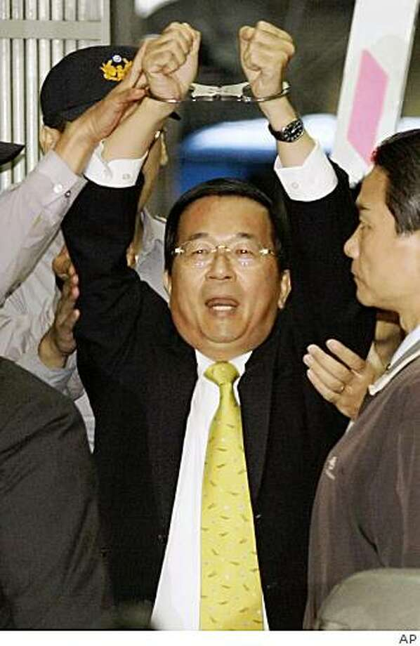 Former Taiwanese President Chen Shui-bian raises his hands with handcuffs as he is led away from the Taiwan prosecutor's office in Taipei, Taiwan, Tuesday, Nov. 11, 2008. Chen was arrested as prosecutors sought formal approval to detain him in connection with corruption allegations. (AP Photo) Photo: STR, AP