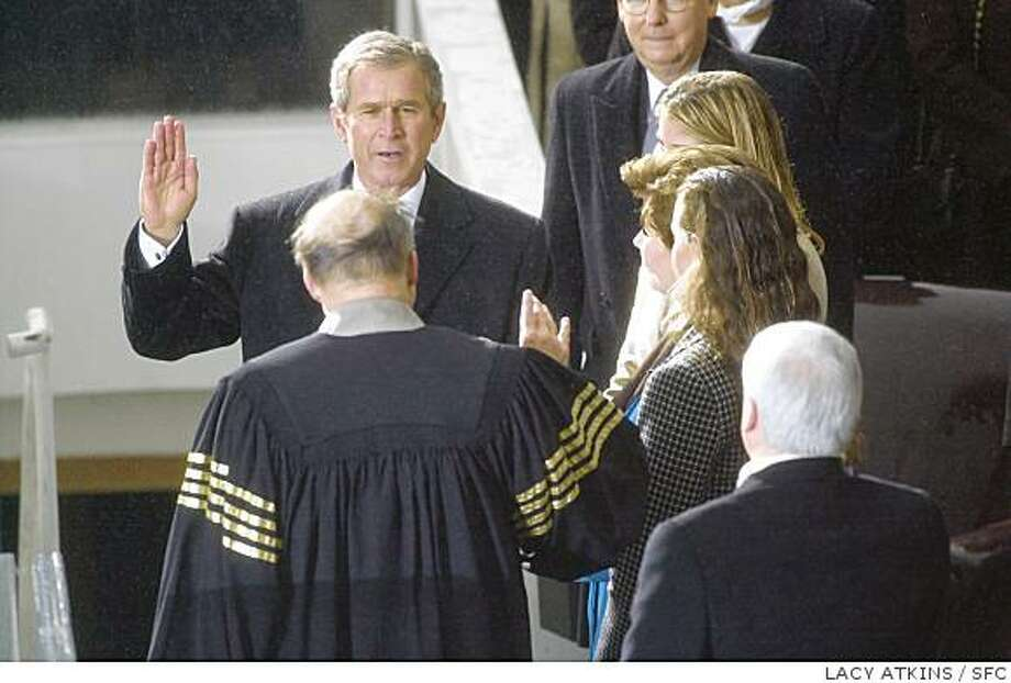 On Jan. 20, 2001, George Bush is sworn in by Chief Judgest William Rehnquist, with his wife and daughters at his side. Photo: LACY ATKINS, SFC