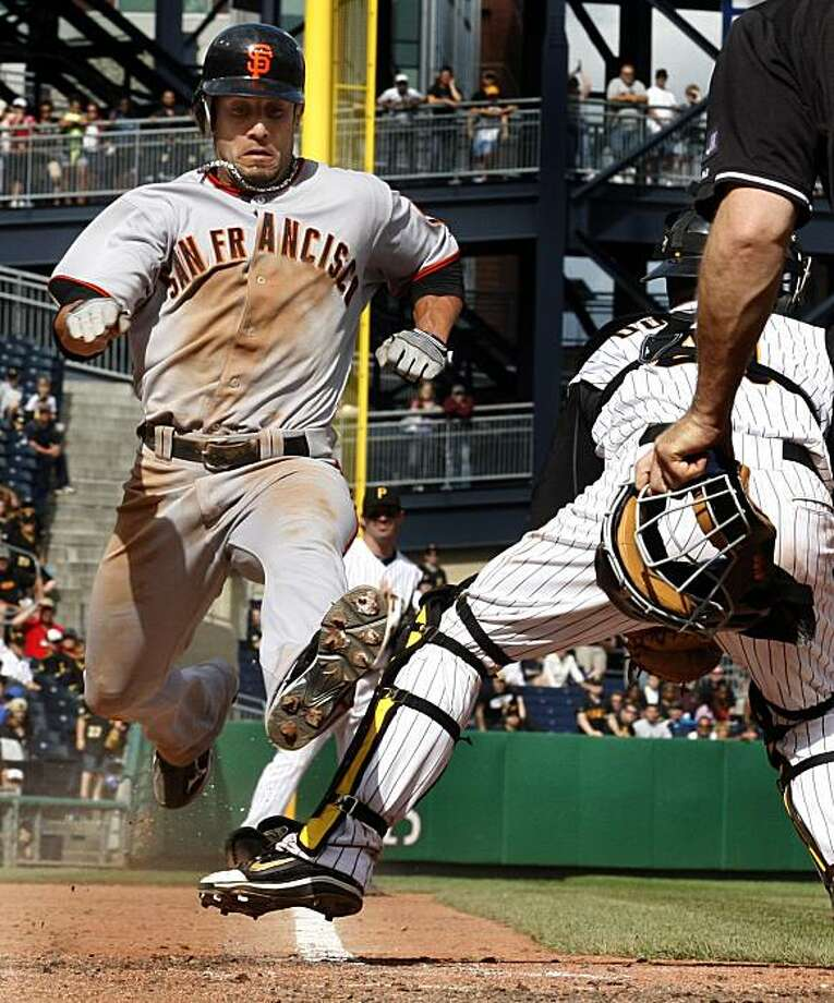 San Francisco Giants' Andres Torres, left, scores over the leg of Pittsburgh Pirates catcher Ryan Doumit on a sacrifice fly by Giants' Freddy Sanchez during the tenth inning of a baseball game in Pittsburgh Sunday, June 6, 2010. The Giants won 6-5 in teninnings. Photo: Gene J. Puskar, AP