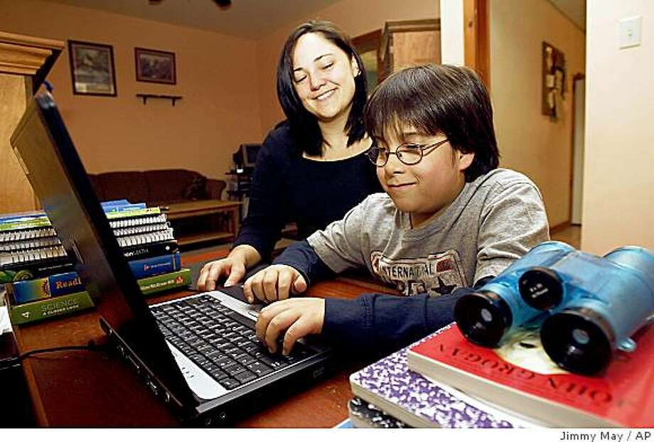 Janice Kraser sits next to her nine-year-old son Billy Kraser at their Scranton, Pa., home Sunday, Nov. 9, 2008, at his computer where his dose his school work. Billy Kraser has spina bifida and has undergone an experimental surgery which reroutes his nerves in attempt to attain normal bladder and bowel function. (AP Photo/Jimmy May) Photo: Jimmy May, AP