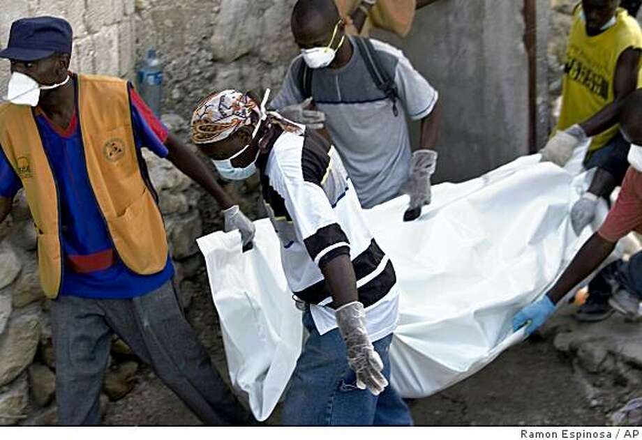 Rescue workers carry a body found in the rubble after 'La Promesse' school collapsed in Petionville, Haiti, Monday, Nov. 10, 2008. U.S., French and Haitian firefighters used sonar, cameras and dogs to scour the wreckage of the school for signs of life three days after it collapsed during a school party, killing about 90 students and adults and severely injuring 150 more.(AP Photo/Ramon Espinosa) Photo: Ramon Espinosa, AP