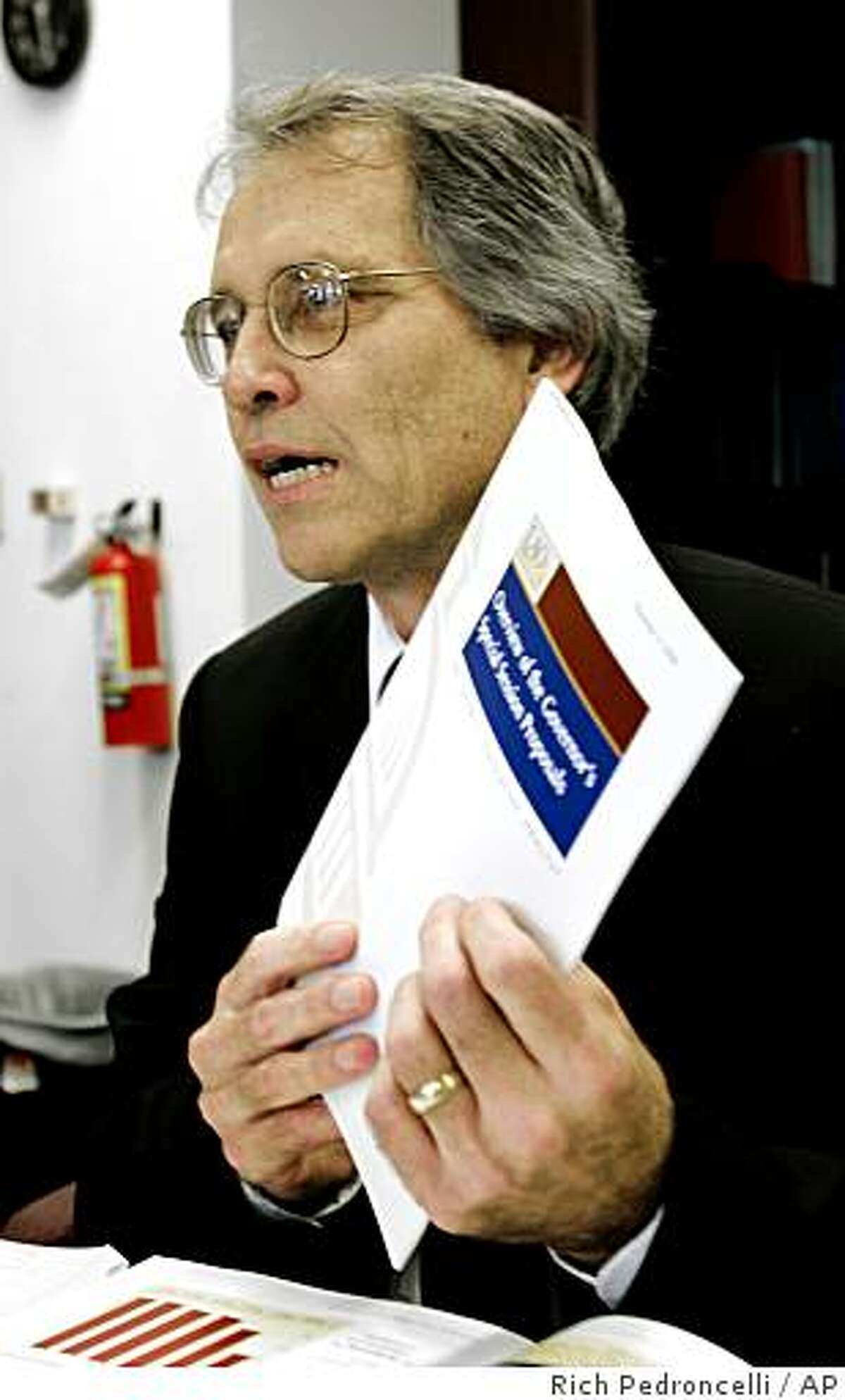 Legislative Analyst Mac Taylor displays a copy of his offices analysis of Gov. Arnold Schwarzeneggers budget proposals during a news conference in Sacramento, Calif., Tuesday, Nov. 11, 2008. Taylor supported the framework of the governor's plan and called it