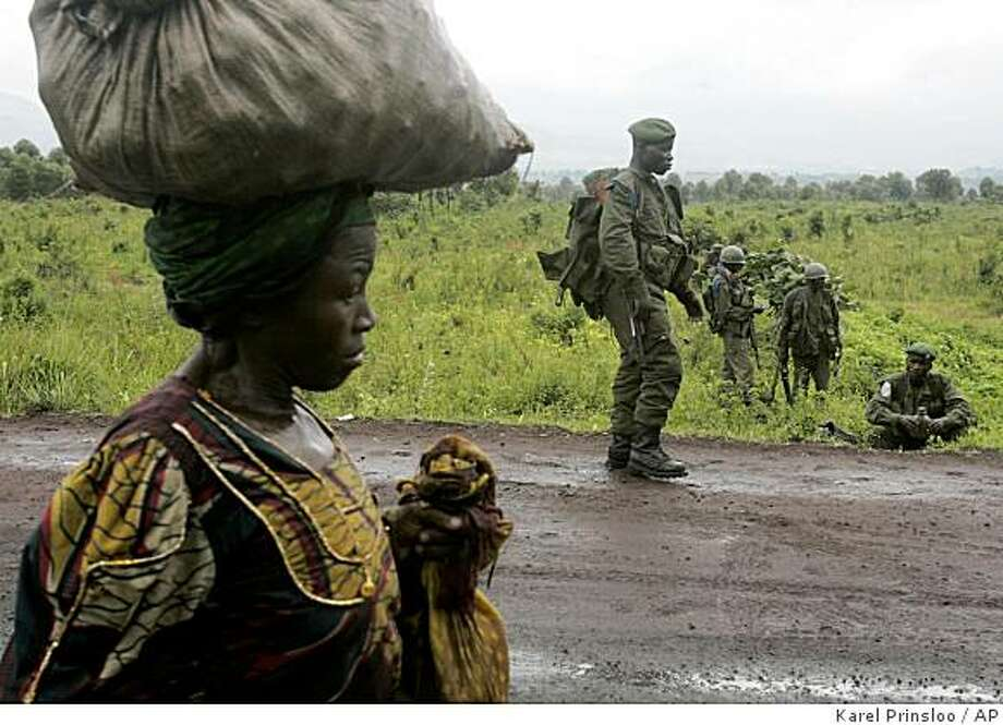 A displaced woman walk past Congolese goverment soldiers on the front line, Wednesday, Nov. 12, 2008 near Kibati just north of Goma in eastern Congo. The city of Goma has been besieged by rebels loyal to renegade Gen. Lauren Nkunda since he reached the outskirts of the provincial capital, and the rebels have promised to fight any African troops that aid the Congolese army.(AP Photo/Karel Prinsloo) Photo: Karel Prinsloo, AP