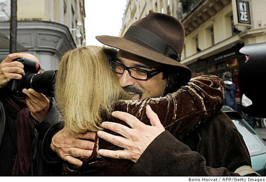 "French-Afghan writer and film director Atiq Rahimi is congratulated by a woman in Paris on November 10, 2008, after receiving France's top book prize, the Goncourt, for a novel penned in French, ""Syngue Sabour"" or ""Stone of Patience"". It is the first novel written in French by 46-year-old Rahimi, best known for his 2002 book ""Earth and Ashes"", which was turned into a film. He was born in Kabul in 1962 and fled the country in the 1980s, first to Pakistan then to France, where he studied film and settled. At right, is Rahimi's wife, christian name unknown. AFP PHOTO BORIS HORVAT (Photo credit should read BORIS HORVAT/AFP/Getty Images) Photo: Boris Horvat, AFP/Getty Images"