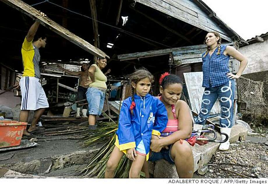People in despair remain on November 9, 2008 in their house, which was destroyed by Hurricane Paloma on its passage over the town of Santa Cruz del Sur, in the eastern Cuban province of Camaguey, 600 km from Havana. Hurricane Paloma weakened Sunday as it stalled over southeastern Cuba after battering the island with lashing rain and gale-force winds. After making landfall on Cuba's southeast coast earlier in the day as a powerful category three hurricane, Paloma quickly declined to a tropical storm and now has winds of 95 km an hour, the US National Hurricane Center informed.  AFP PHOTO/ADALBERTO ROQUE (Photo credit should read ADALBERTO ROQUE/AFP/Getty Images) Photo: ADALBERTO ROQUE, AFP/Getty Images