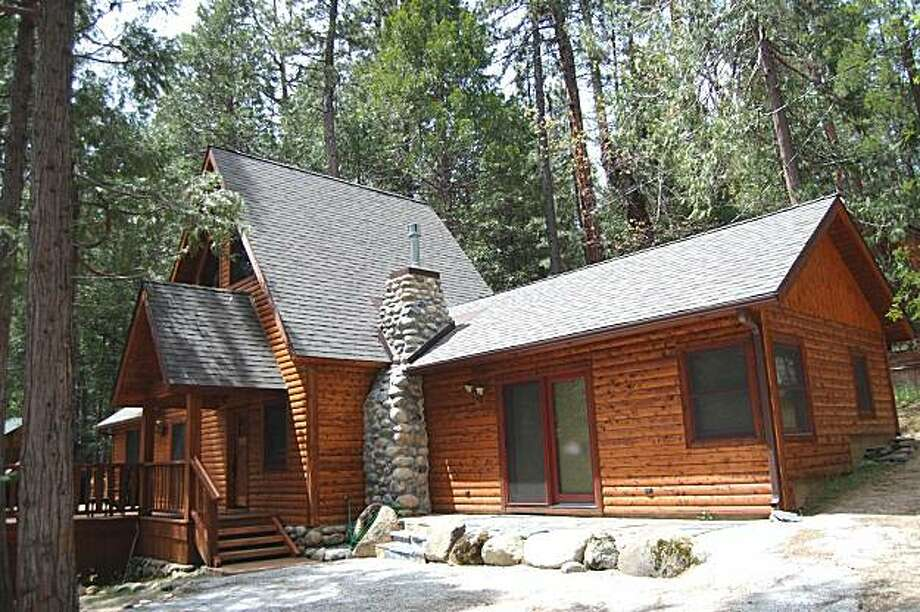 One of the 131 vacation home cabins that comprise The Redwoods in Yosemite. This one has three bedrooms. two baths and -- for that extra special woodsy feel -- three flat-screen TVs. Photo: Courtesy/The Redwoods
