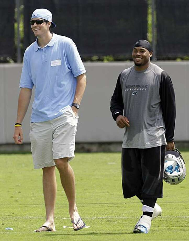 Carolina Panthers' Steve Smith, right, laughs with tennis player John Isner, left, after football practice in Charlotte, N.C., Wednesday, June 2, 2010. Photo: Chuck Burton, AP