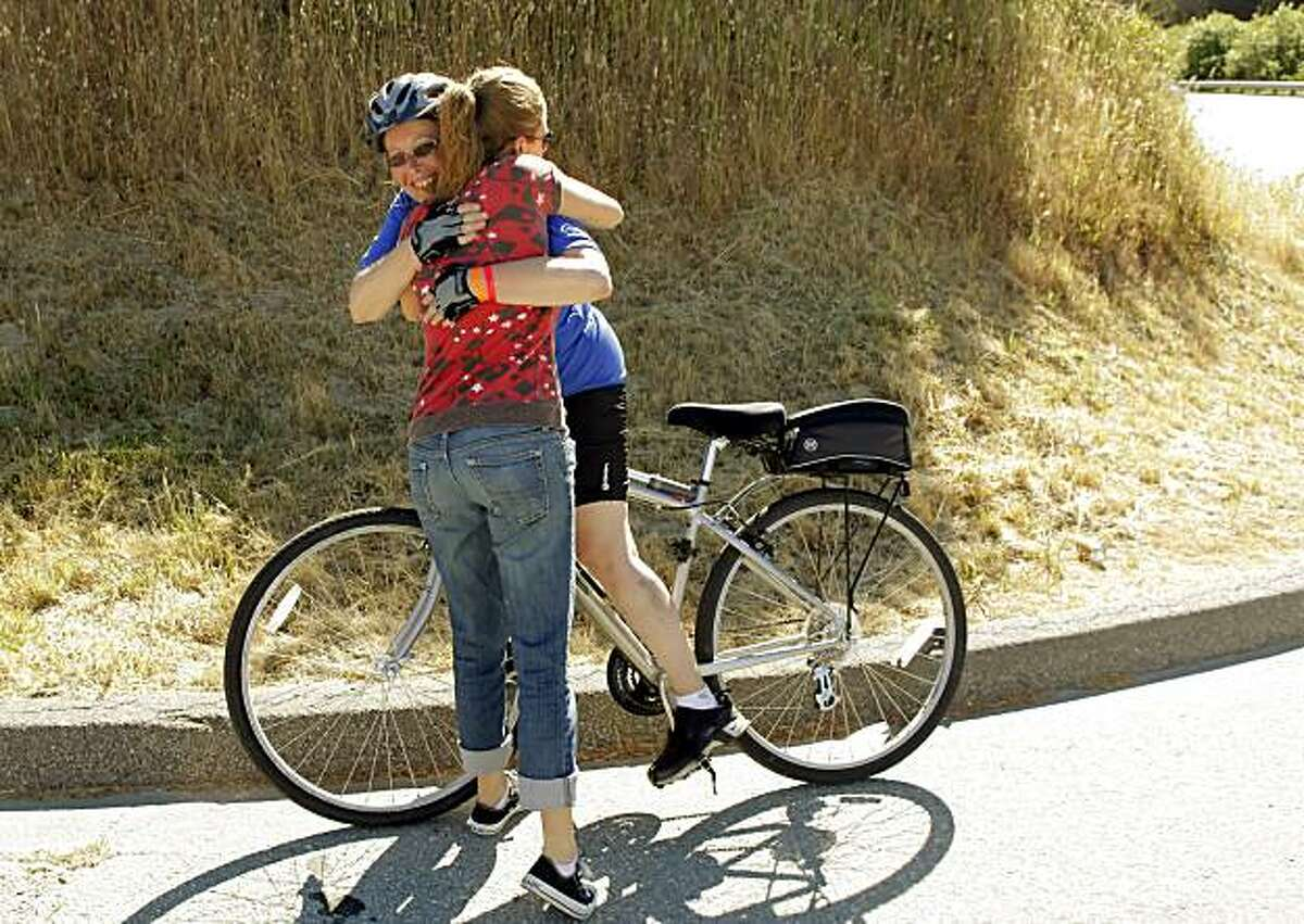 Barbara Hansen of Chicago gets a hug from her daughter, Louisa Galassini of San Francisco, as she arrives at Rest Stop 4 on the first day of the AIDS/Lifecycle ride Sunday.