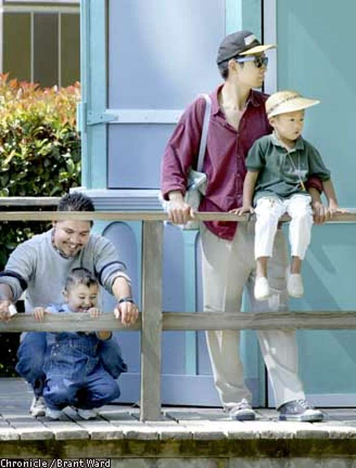 Waiting for the train at San Jose's Happy Hollow Zoo, Tieniu Li, right standing, and his four and a half year old son Alan struck a handsom pose. Both were born in Beijing but now make their homes in the southbay. Meanwhile, Leonel Cordova, left, got the giggles with his nephew. Cordova was born in Mexico. They were within a stones throw of the census tract in San Jose with the largest population of foreign-born citizens. By Brant Ward/Chronicle Photo: BRANT WARD