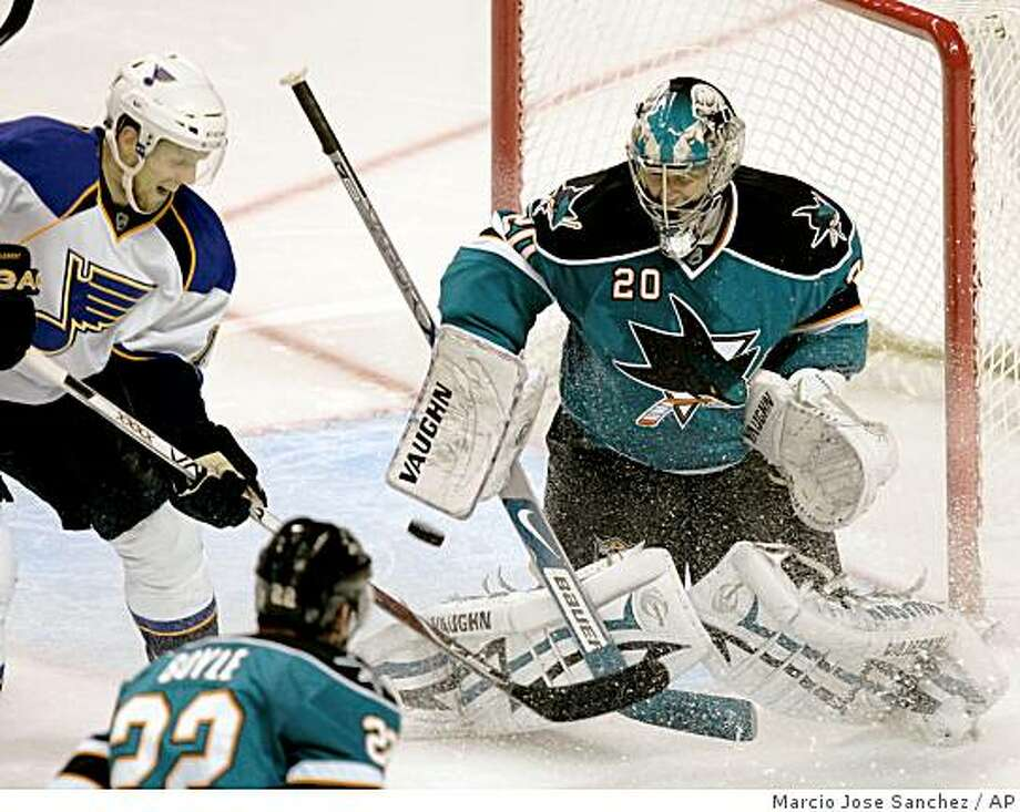 San Jose Sharks goalie Evgeni Nabokov, of Kazakhstan, stops a shot by St. Louis Blues center Jay McClement, left, during the second period of an NHL hockey game in San Jose, Calif. Thursday, Nov. 6, 2008. (AP Photo/Marcio Jose Sanchez) Photo: Marcio Jose Sanchez, AP