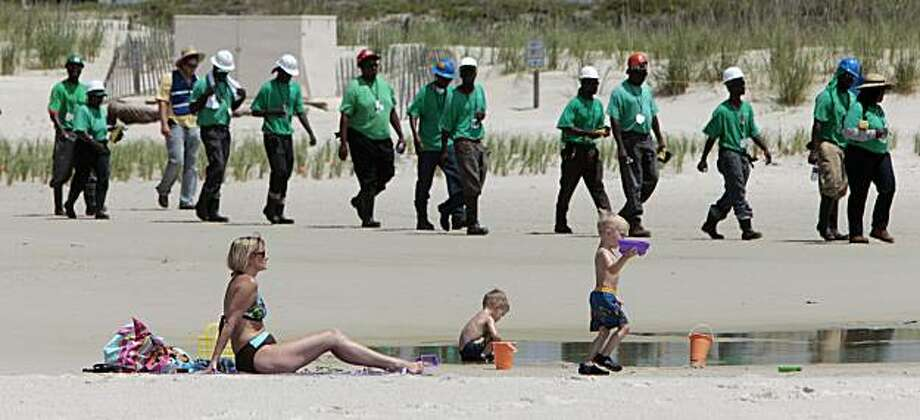 Mary Smith of Theodore, Ala., watches over her grandchildren as a large crew of clean up workers walk along the beach in Dauphin Island, Ala., Tuesday, June 2, 2010. Oil from the Deepwater Horizon disaster has started washing ashore on the Alabama coast. Photo: Dave Martin, AP