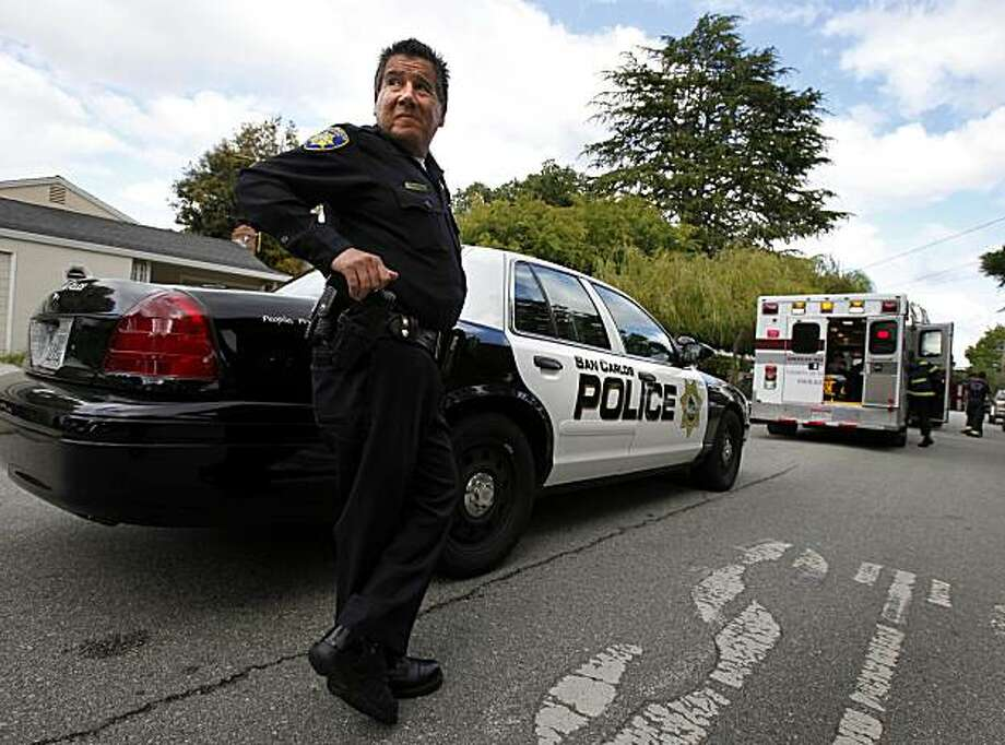 Officer Ed Estrada watches traffic as he assists an ambulance crew called to a day care center Thursday May 27, 2010. Ed Estrada, who has been in law enforcement over 20 years, is one of only four officers in the San Carlos police. The San Carlos, Calif. police department is in danger of being disbanded because of budget cuts. Photo: Brant Ward, The Chronicle