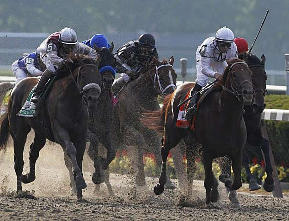 Jockey Mike Smith, right in white, approaches the finish line atop Drosselmeyer to win the 142nd running of the Belmont Stakes at Belmont Park in Elmont, N.Y., Saturday, June 5, 2010. Photo: Kathy Willens, AP