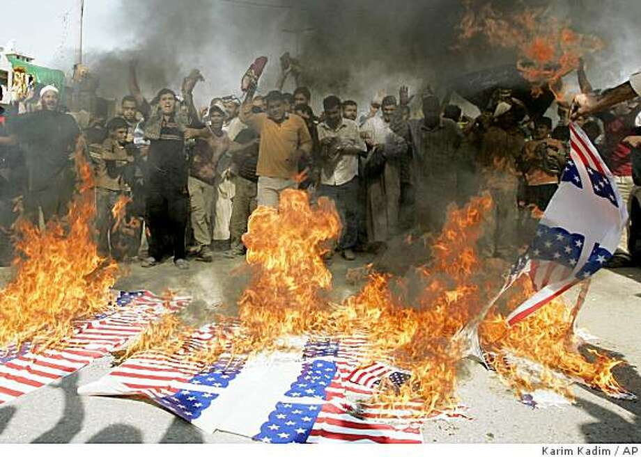 Supporters of radical cleric Muqtada al-Sadr burn symbolic American flags as they demonstrate against the proposed security pact between Iraq and the U.S., in Baghdad's Shiite stronghold of Sadr City, Iraq, Friday, Nov. 7, 2008. The U.S. responded Thursday to Iraqi proposals for changes in the draft security pact that would keep U.S. troops in Iraq for three more years, saying the text is final and it's up to the Iraqis to push the process to approval. (AP Photo/Karim Kadim) Photo: Karim Kadim, AP