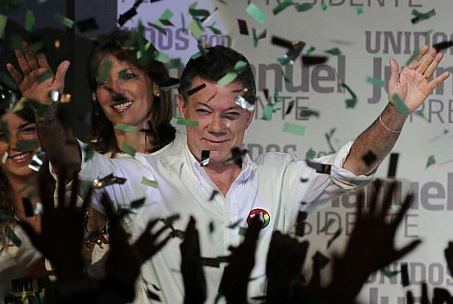 Under a rain of confetti, presidential candidate of the Social National Unity Party, Juan Manuel Santos, gestures to supporters in Bogota, Sunday, May 30, 2010.  Santos, a conservative former defense minister who promises to build on Alvaro Uribe's security gains, defeated Antanas Mockus, who runs for the Green Party, in Colombia's election Sunday but fell short of the votes needed to avoid a presidential runoff. Photo: Fernando Vergara, AP
